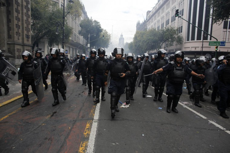 Riot policemen walk toward the Zocalo after protesters had been given a deadline to evacuate. (Tomas Bravo / Reuters)