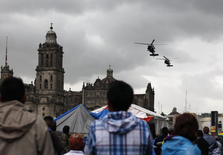 Protesters look at helicopters of the federal police as they fly over the Zocalo in Mexico City. (Tomas Bravo / Reuters)
