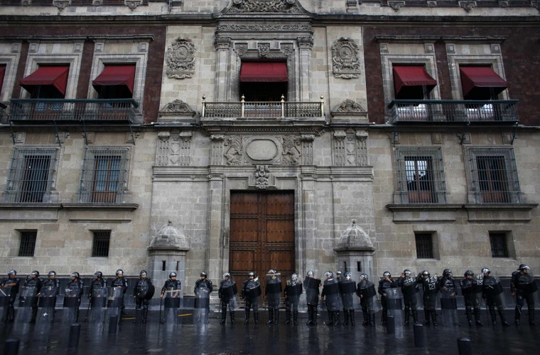Police stand outside the former presidential palace and underneath the balcony where Mexico's President Enrique Pena Nieto is due to lead his first traditional remembrance of the heroes of Mexican independence. Police used tear gas and water cannons to disperse demonstrators in the main square of Mexico City, arresting 31 people, as the government took control of the historic center after weeks of protests by teachers. (Tomas Bravo / Reuters)