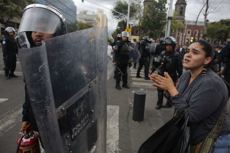 A woman pleads for no additional violence to a riot police officer after striking members of the teachers' union CNTE were evicted from Zocalo Square in downtown Mexico City. (Tomas Bravo / Reuters)