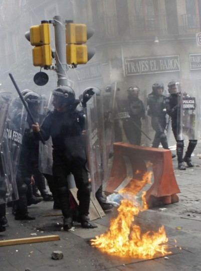 Riot policemen take cover with their shields during a clash with protesters as striking members of the teachers' union CNTE are evicted from Zocalo Square in downtown Mexico City. (Henry Romero / Reuters)