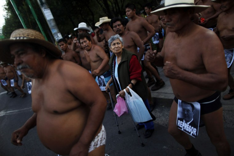 """A woman reacts before crossing the street during a demonstration by peasants dancing in their underwear to demand an audience with the Federal District authorities in Mexico City, September 12, 2013. The protesters belong to a group called the """"400 villages,"""" who are demanding for land that they claim was unjustly taken away from them in Tabasco. (Edgard Garrido/Reuters)"""
