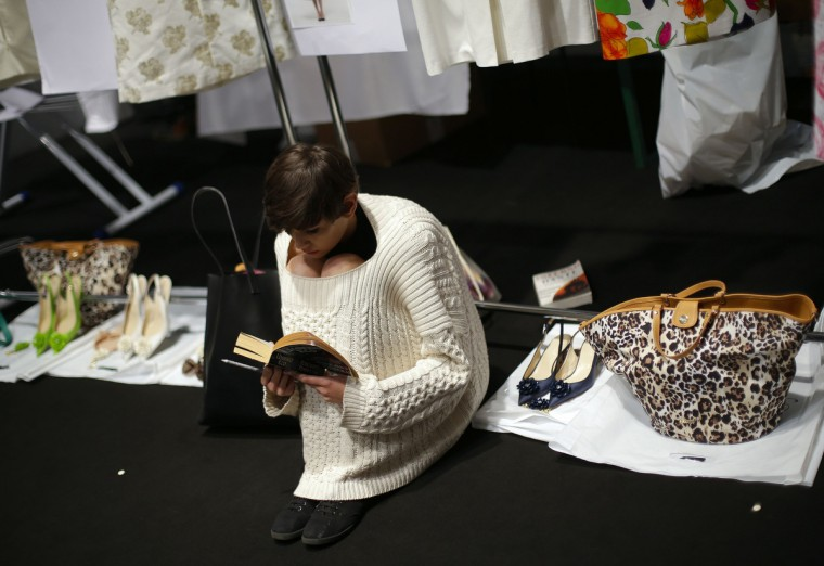 A model reads a book backstage at the presentation of the Blugirl Spring/Summer 2014 collection during Milan Fashion Week. (Max Rossi/Reuters photo)