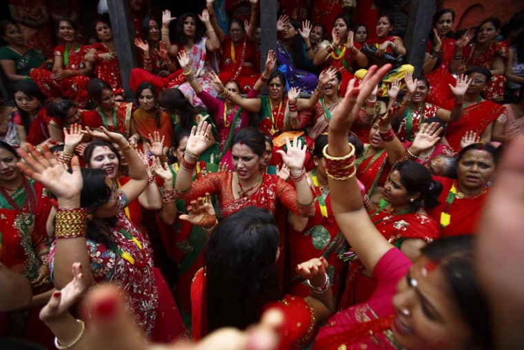 Women sing and dance at Pashupatinath Temple during the Teej festival in Kathmandu September 8, 2013. The three-day festival, commemorating the union of Goddess Parvati and Lord Shiva, involves sumptuous feasts and rigid fasting. Hindu women pray for marital bliss, the well-being of their spouses and children, and the purification of their own bodies and souls during this period of religious fasting. (Navesh Chitrakar/Reuters)