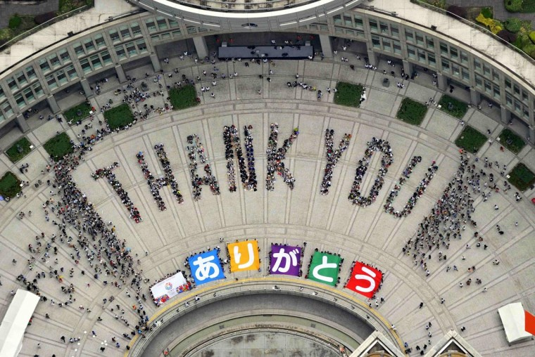 """An aerial view shows people sitting in formation to the words """"thank you"""" and displaying signs that collectively read """"Arigato"""" (Thank You) during an event celebrating Tokyo being chosen to host the 2020 Olympic Games, at Tokyo Metropolitan Government Building in Tokyo, in this photo taken by Kyodo September 8, 2013. (Kyodo via Reuters)"""