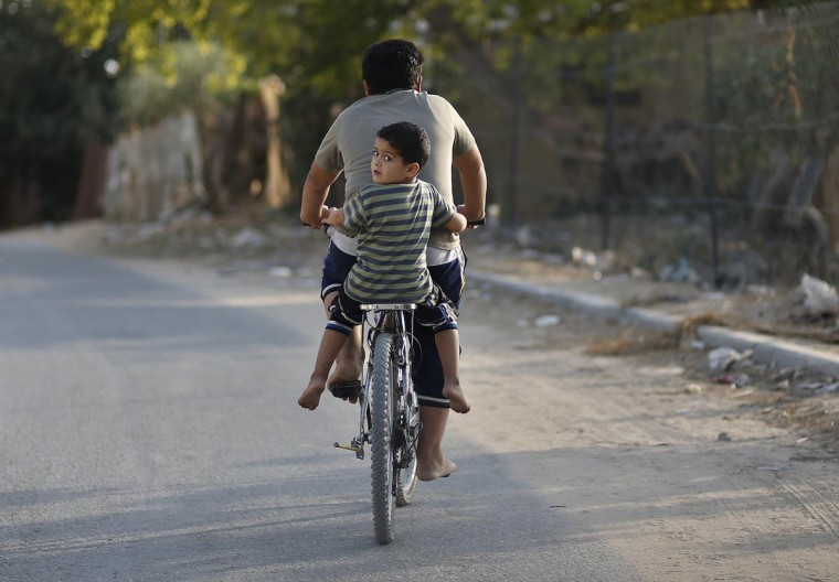 A Palestinian boy rides a bicycle with his brother on a street in the northern Gaza Strip September 3, 2013. (Mohammed Salem/Reuters)