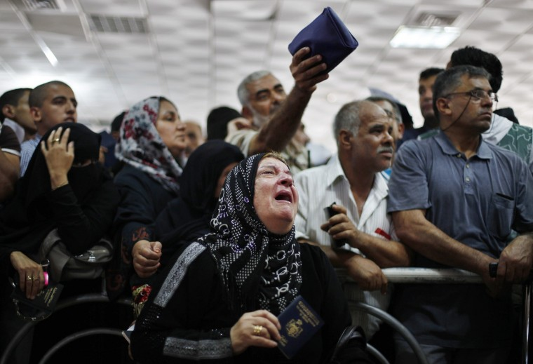 A passenger cries as she waits at the Rafah crossing between Egypt and southern Gaza Strip with hopes of crossing into Egypt. Egypt partially reopened its border crossing with the Gaza Strip on a week after it was closed in response to a deadly attack on an Egyptian military headquarters near the frontier. (Ibraheem Abu Mustafa/Reuters photo)