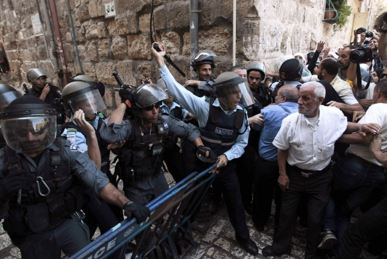 An Israeli policeman (L) shouts at Palestinian demonstrators near Lion's Gate in Jerusalem's Old City, as minor clashes take place at a nearby compound known to Muslims as Noble Sanctuary and to Jews as Temple Mount. An Israeli police spokesperson said five people were detained on Wednesday for throwing stones at police who had entered the compound after stones were thrown at visitors at the holy site ahead of the Jewish new year, or Rosh Hashanah, which begins today at sundown. (Ammar Awad/Reuters)