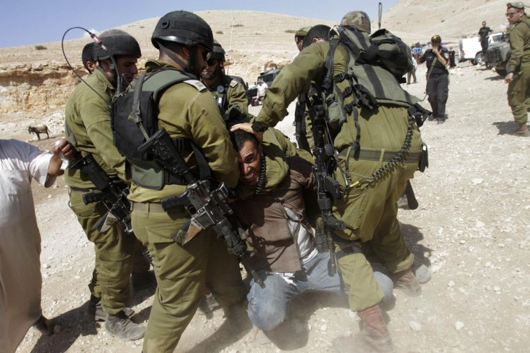 Israeli soldiers detain a Palestinian during scuffles following an attempt by European diplomats to deliver goods to locals in the West Bank herding community of Khirbet al-Makhul, in the Jordan Valley September 20, 2013. (Abed Omar Qusini/Reuters)