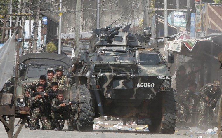 Government soldiers take cover during a firefight with Muslim rebels from the Moro National Liberation Front (MNLF) in Zamboanga city in southern Philippines. Fighting between security forces and rogue Muslim rebels seeking to declare an independent state escalated in a southern Philippine city on Thursday and spread to a second island, officials said. U.S.-trained commandos exchanged gunfire with a breakaway faction of the MNLF holding dozens of hostages in Zamboanga City, on the southernmost island of Mindanao, army spokesman Domingo Tutaan said. (Erik De Castro/Reuters)