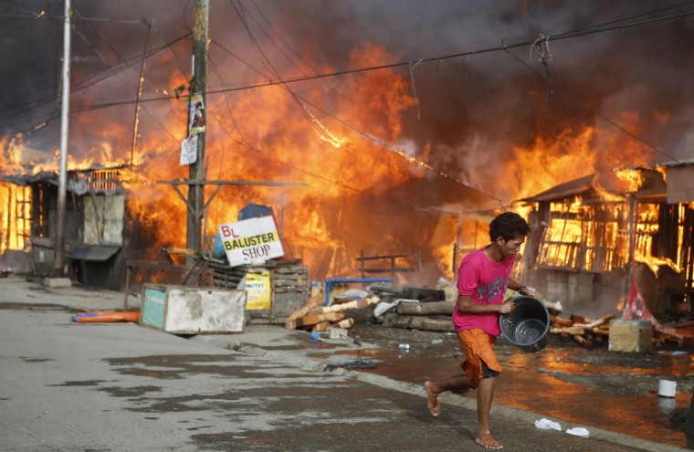 A man runs to fetch water to douse burning houses in a residential district, caused by a firefight between government soldiers and Muslim rebels from the Moro National Liberation Front (MNLF), in Zamboanga city in southern Philippines. Fighting between security forces and rogue Muslim rebels seeking to declare an independent state escalated in a southern Philippine city on Thursday and spread to a second island, officials said. U.S.-trained commandos exchanged gunfire with a breakaway faction of the MNLF holding dozens of hostages in Zamboanga City, on the southernmost island of Mindanao, army spokesman Domingo Tutaan said. (Erik De Castro/Reuters)