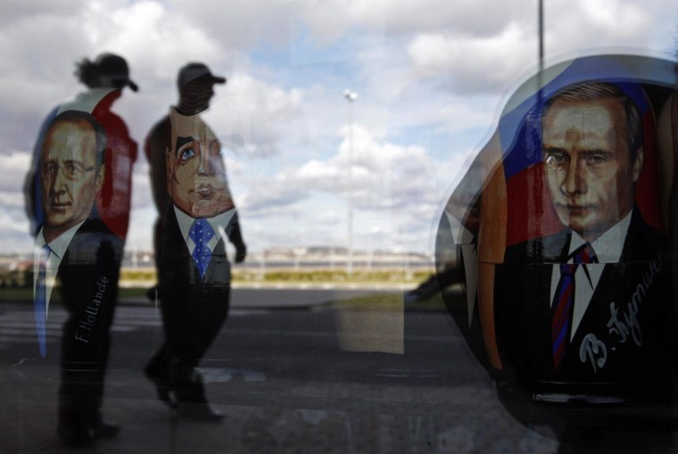 Police are reflected in the window of a shop displaying traditional nesting dolls with images of Russian President Vladimir Putin (R), Prime Minister Dmitry Medvedev (C) and French President Francois Hollande at the sea port in St. Petersburg September 3, 2013. Russia's second city will host the G20 summit this week. (Alexander Demianchuk/Reuters)