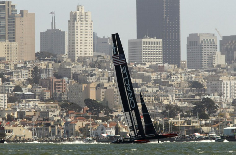 Oracle Team USA sails near the city skyline against Emirates Team New Zealand during Race 18 of the 34th America's Cup yacht sailing race. (Reuters / Robert Galbraith)