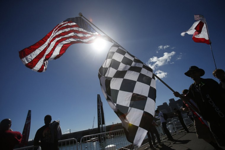 A sailing fan carries an American flag before Race 19 of the 34th America's Cup yacht sailing race between Oracle Team USA and Emirates Team New Zealand in San Francisco. (REUTERS/Stephen Lam)