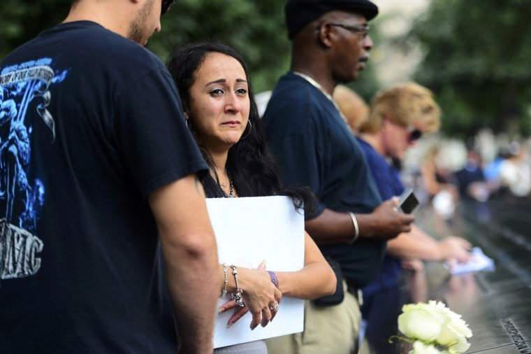 Mercedes Arias listens as they read the name of her father Joseph Amatuccio at the 9/11 Memorial during ceremonies marking the 12th anniversary of the 9/11 attacks on the World Trade Center in New York September 11, 2013. (Alejandra Villa/Reuters)