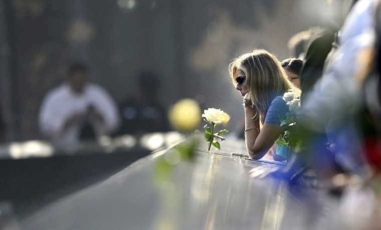 A woman pauses along the edge of the North Pool of the 9/11 Memorial during a ceremony marking the 12th anniversary of the 9/11 attacks on the World Trade Center in New York, September 11, 2013. (Justin Lane/Reuters)