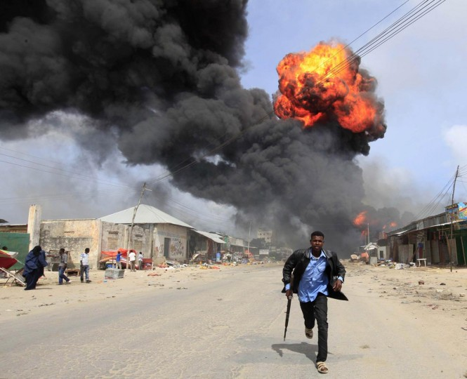 A Somali policeman runs from the scene of an accidental explosion at a petrol storage facility within the former United States residential housing in capital Mogadishu, September 3, 2013. (Feisal Omar/Reuters)