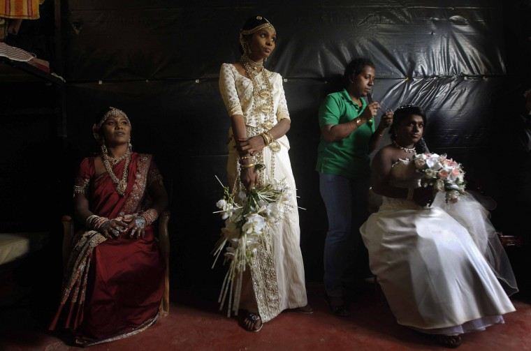 Former Tamil Tiger (LTTE) female rebel fighters and brides Nadarasa Sukirtha (L) and Premarathnam Sugandhini (C) look on as Jayarasa Merry Babila, an ethnic Tamil, gets ready before the start of a mass wedding in Kilinochchi, about 334 km (208 miles) northeast of Colombo. Three ex-rebel couples who have been rehabilitated by the Sri Lankan Civil Defence Force were married in a mass wedding ceremony as part of the government's rehabilitation program. Sri Lanka's government troops defeated the LTTE after a 25-year civil struggle. (Dinuka Liyanawatte/Reuters)