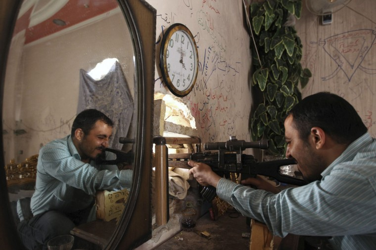 A Free Syrian Army fighter points his weapon through a hole from inside a house in the old city of Aleppo. (Muzaffar Salman/Reuters)