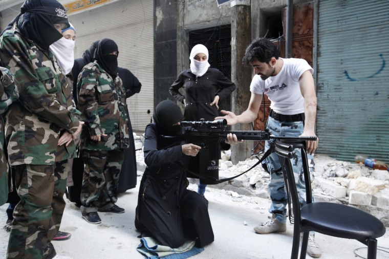 """A female member of the """"Mother Aisha"""" battalion receives instruction as she holds a rifle during military training in Aleppo's Salaheddine district. (Loubna Mrie/Reuters photo)"""