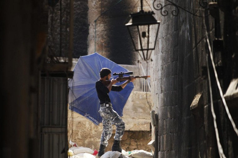 A Free Syrian Army fighter aims his weapon as he takes a defensive position in the old city of Aleppo, September 3, 2013. (Muzaffar Salman/Reuters)