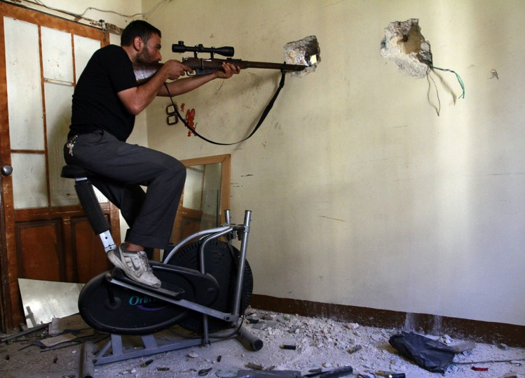 A Free Syrian Army fighter takes a position as he aims his weapon at the Justice Palace, which is controlled by forces loyal to Syria's President Bashar al-Assad, in Aleppo September 13, 2013. (Hamid Khatib/Reuters)