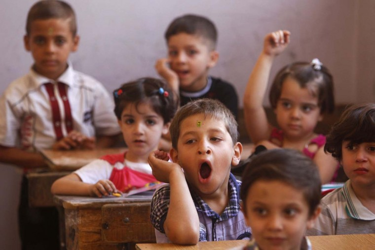 A pupil yawns as he sits in a classroom at the start of the new school year in the city of Aleppo September 16, 2013. (Muzaffar Salman/Reuters)