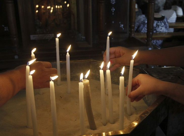 Syrian women light candles before attending mass in the Catholic Patriarchate in Damascus, September 7, 2013. Pope Francis has urged the international community to join in a special day of fasting and prayer for peace in Syria on Saturday. (Khaled al Hariri/Reuters)