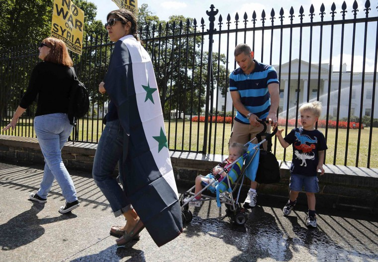 Protesters, including one wearing a Syrian flag, walk past a family of tourists as they rally against proposed U.S. military action in Syria in front of the White House in Washington, September 7, 2013. (Jonathan Ernst/Reuters)