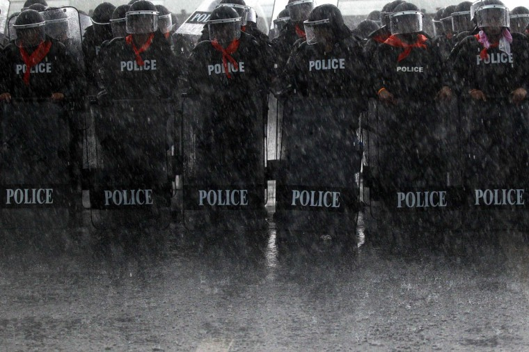 Heavy rain falls on policemen taking positions as rubber farmers protest near the airport in Surat Thani. Tens of thousands of Thai rubber farmers protesting against a sharp drop in prices escalated protests across southern Thailand on Wednesday, cutting off access to large swathes of the region by blocking roads leading to tourist and commercial hubs. (Athit Perawongmetha/Reuters)