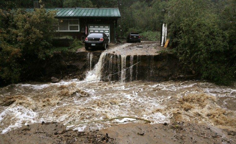 A home and car are stranded after a flash flood in Coal Creek destroyed the bridge near Golden, Colorado. Flooding in Colorado left two people dead, prompted hundreds to be evacuated, caused building collapses and stranded cars, officials said. (Rick Wilking/Reuters)