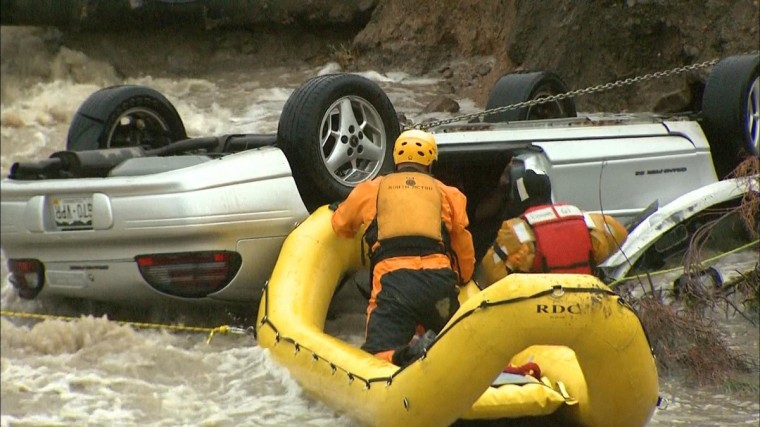 Emergency personnel work to rescue a man trapped in his vehicle during a flooding of Rock Creek in Lafayette, Colorado. The National Weather Service has issued a flash flood warning for central Boulder County that will remain in effect through at least 10 a.m. local time. (CBS4 Denver/Reuters)