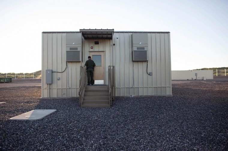 A border patrol agent opens the entrance to a temporary holding facility at the U.S. Department of Homeland Security's Forward Operating Base (FOB) Hedglen located southeast of Douglas, Arizona August 8, 2013. Modeled on the remote fire bases used by the U.S. military in Afghanistan, the 10-acre (four-hectare) fence-ringed facility in Arizona's high desert is the U.S. government's latest bid to plug the remaining gaps on the porous border with Mexico. (Samantha Sais/Reuters)