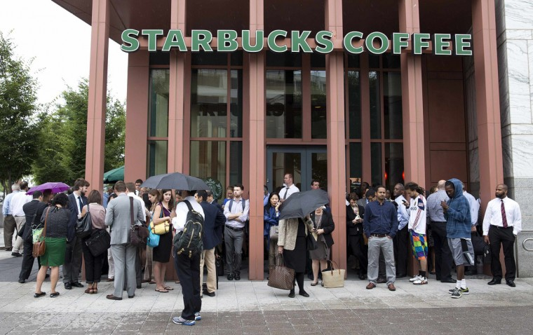 People stand outside a Starbucks Coffee shop that has been closed as police respond to a shooting at the Washington Navy Yard in Washington, September 16, 2013. The U.S. Navy said several people were injured and there were possible fatalities in the shooting at the Navy Yard in Washington D.C. on Monday. The Navy did not immediately provide additional details but a Washington police spokesman said earlier that five people had been shot, including a District of Columbia police officer and one other law enforcement officer. (Joshua Roberts/Reuters)