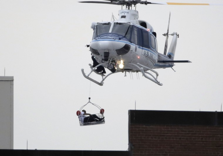 A helicopter pulls what appears to be a shooting victim up as it hovers over a rooftop on the Washington Navy Yard campus in Washington, September 16, 2013. The U.S. Navy said several people were injured and there were possible fatalities in the shooting at the Navy Yard in Washington D.C. on Monday. The Navy did not immediately provide additional details but a Washington police spokesman said earlier that five people had been shot, including a District of Columbia police officer and one other law enforcement officer. (Jason Reed/Reuters)