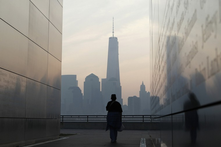 A woman looks out at New York's Lower Manhattan and One World Trade Center from inside the 9/11 Empty Sky memorial at Liberty State Park in Jersey City, New Jersey, September 11, 2013. Americans commemorate the 12th anniversary of the September 11 attacks with solemn ceremonies and pledges to not forget the nearly 3,000 killed when hijacked jetliners crashed into the World Trade Center, the Pentagon, and a Pennsylvania field. (Gary Hershorn/Reuters)