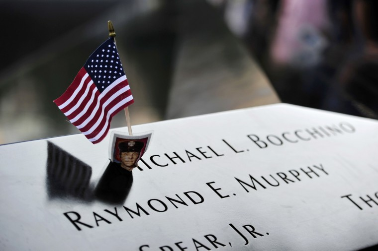 A flag and photograph of New York City Fire Department fire fighter Michael L. Bocchino is placed on his name at the South reflecting pool at the 9/11 Memorial during ceremonies marking the 12th anniversary of the 9/11 attacks on the World Trade Center in New York, September 11, 2013. (Stan Honda/Reuters)
