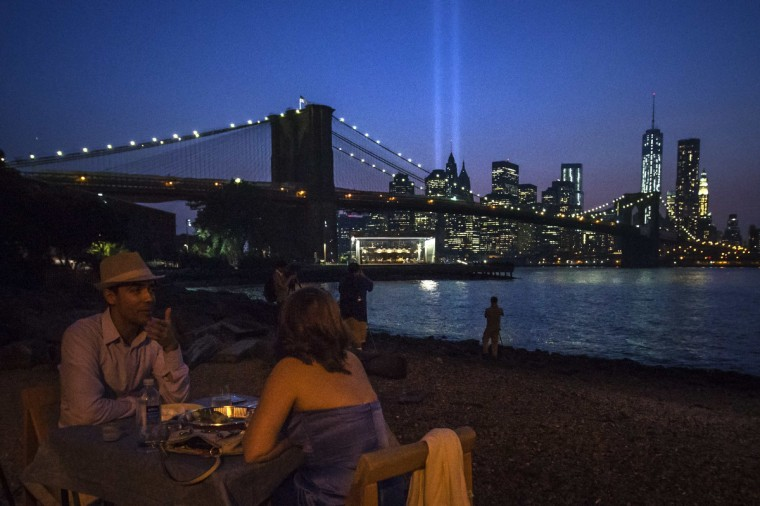A couple enjoys dinner over looking the Brooklyn Bridge as the Tribute in Light illuminates the sky over the Lower Manhattan skyline a day ahead of the 12-year anniversary of the 9/11 attacks in the Brooklyn borough of New York on September 10, 2013. (Adrees Latif/Reuters)