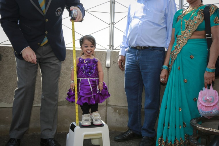 "Jyoti Amge,19, from Nagpur, India, is measured by a Guinness World Record official on top of the Empire State Building in New York. Standing 24.7 inches tall, Amge has held the title of the ""Shortest Living Woman"" since her 18th birthday on December 16, 2011. (Shannon Stapleton/Reuters)"