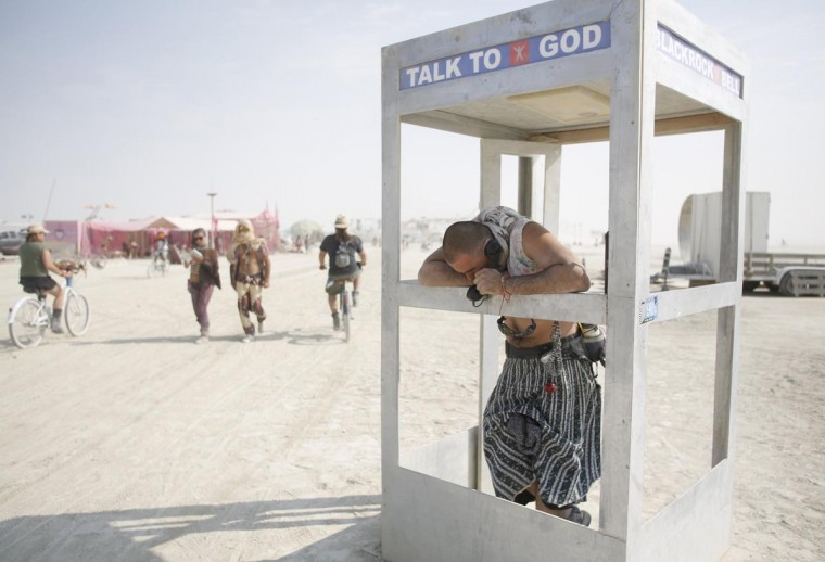 Pippin, his Playa name, chats on the phone with God during the Burning Man 2013 arts and music festival in the Black Rock Desert of Nevada, September 1, 2013. (Jim Urquhart/Reuters)