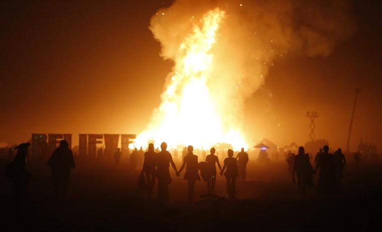 Burning Man participants walk towards the Temple of Whollyness as it burns at the conclusion of the 2013 Burning Man arts and music festival in the Black Rock desert of Nevada, late September 1, 2013. (Jim Bourg/Reuters)