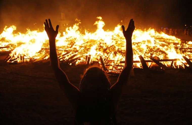A Burning Man participant pays homage to the Temple of Whollyness as it burns at the conclusion of the 2013 Burning Man arts and music festival in the Black Rock desert of Nevada, late September 1, 2013. (Jim Bourg/Reuters)
