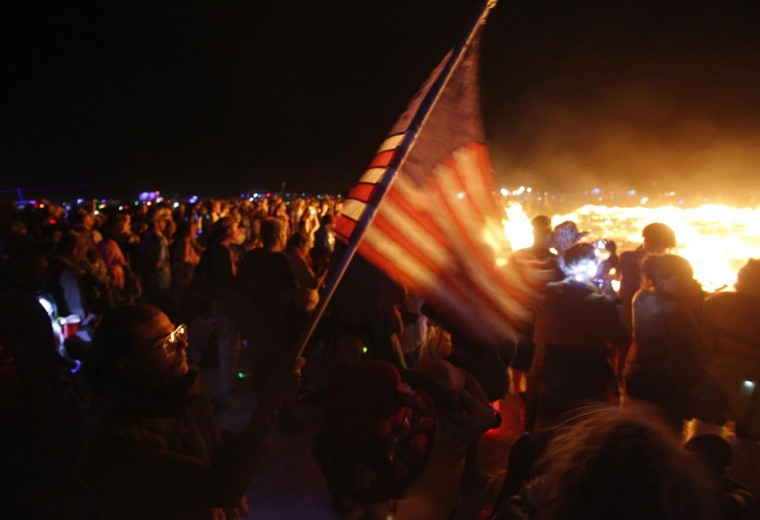 Spectrum, his Playa name, flies an American flag as the Temple of Whollyness is burned during the Burning Man 2013 arts and music festival in the Black Rock Desert of Nevada September 1, 2013. (Jim Urquhart/Reuters)