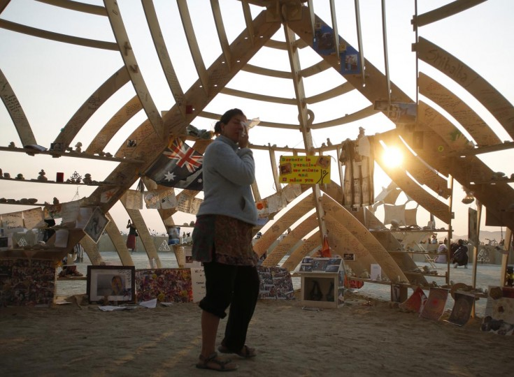 Jamie Singer weeps as she walks through the Temple of Whollyness at sunrise during the Burning Man 2013 arts and music festival in the Black Rock Desert of Nevada, August 31, 2013. (Jim Urquhart/Reuters)