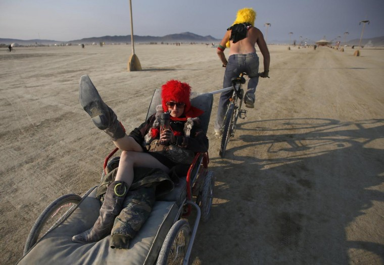 Christin Meador is towed along the Playa by Adam Johnson at sunrise during the Burning Man 2013 arts and music festival in the Black Rock Desert of Nevada, August 31, 2013. (Jim Urquhart/Reuters)