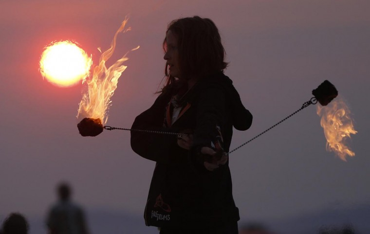 Krissy Humphreys performs with fire at sunrise at the Temple of Whollyness during the Burning Man 2013 arts and music festival in the Black Rock Desert of Nevada, August 31, 2013. (Jim Urquhart/Reuters)