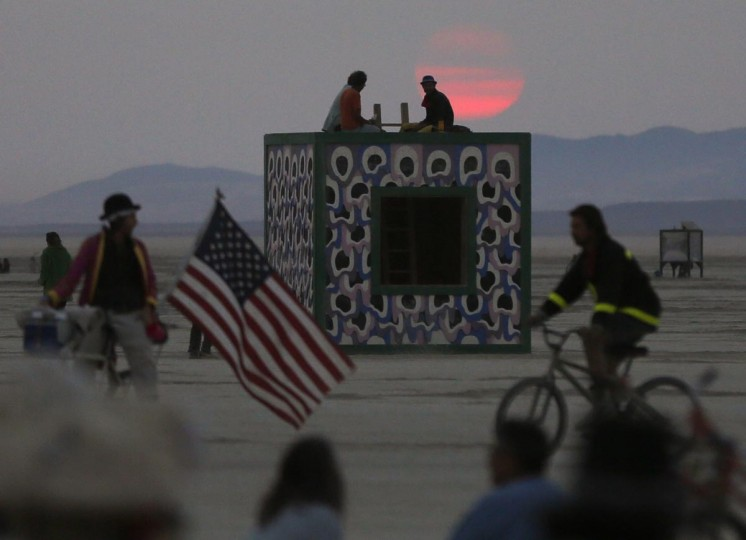 Participants watch the sunrise from atop an art installation during the Burning Man 2013 arts and music festival in the Black Rock Desert of Nevada, August 31, 2013. (Jim Urquhart/Reuters)