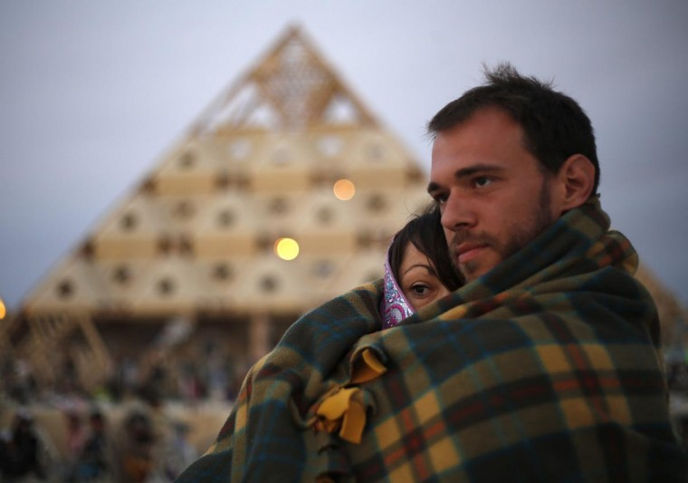 Katherine Cadger and Kevin Rae watch the sunrise at the Temple of Whollyness during the Burning Man 2013 arts and music festival in the Black Rock Desert of Nevada August 31, 2013. (Jim Urquhart/Reuters)