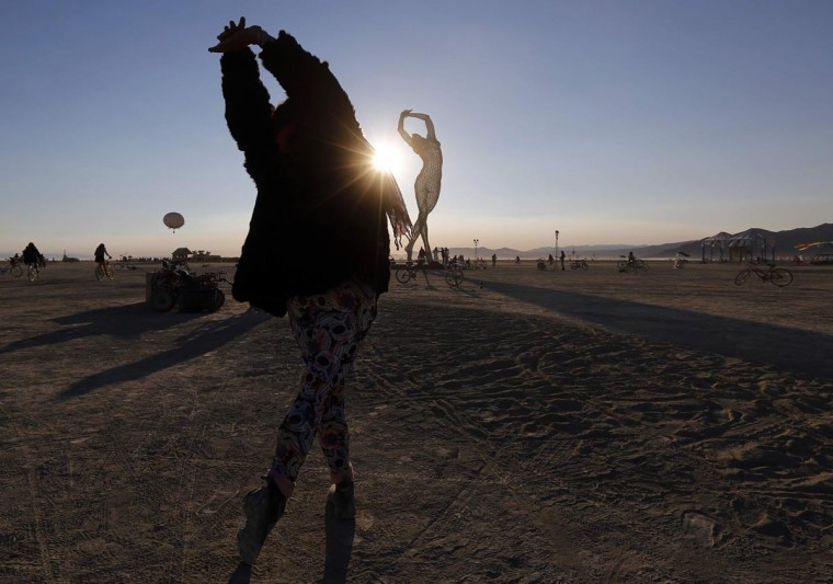 "Rochelle Schieck dances by the ""Truth is Beauty"" sculpture created by Marco Cochrane at the 2013 Burning Man arts and music festival in the Black Rock desert of Nevada, August 30, 2013. (Jim Bourg/Reuters)"