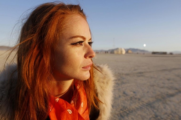 "Alexandra Aguilera, who goes by the playa name ""Crazy Rouge,"" and flew to her first burn from her current home in Hong Kong, looks out at the light of the rising sun at the 2013 Burning Man arts and music festival in the Black Rock desert of Nevada, August 30, 2013. (Jim Bourg/Reuters)"